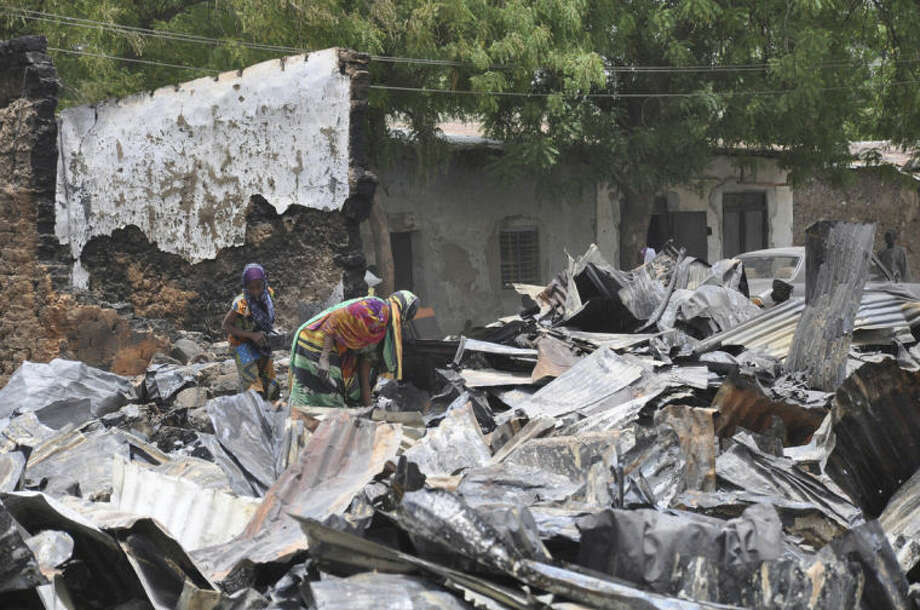 In this photo taken Sunday, May 11, 2014, women search for valuables at a burnt out house following an attack by Islamic militants in Gambaru, Nigeria. Many brutalized residents of the once bustling town of Gamboru said Monday May 12, 2014, they are moving across the border to Cameroon because they cannot trust the Nigerian government to protect them, after repeated attacks by Islamic militants, including an attack a few days ago that killed some hundreds of people with more than 1,000 shops, dozens of homes and 314 trucks and cars bombed and burned out.(AP Photo/Jossy Ola)