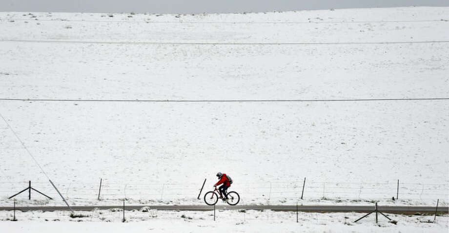 A biker passes fresh snow from the fringe of a major spring snowstorm in the nearby mountains, in Superior, Colo., on Monday, May 12, 2014. A spring storm has brought up to 3 feet of snow to the Rockies and severe thunderstorms and tornadoes to the Midwest. In Colorado, the snow that began falling on Mother's Day caused some power outages as it weighed down newly greening trees. (AP Photo/Brennan Linsley)