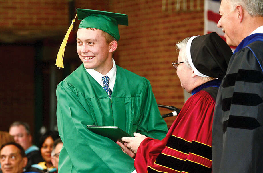 Hour photo / Erik Trautmann Mathew Carlson receives his diploma during commencement excercises for Trinity Catholic High Schools Class of 2015 Saturday.