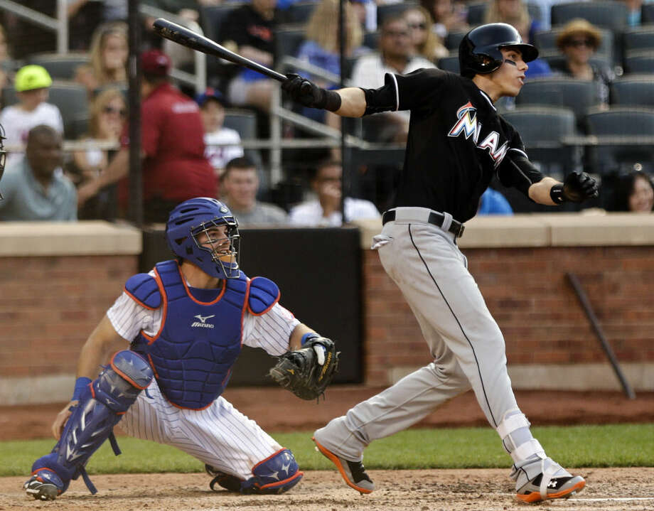 Miami Marlins' Christian Yelich follows through with a two-run single during the seventh inning of a baseball game as New York Mets catcher Kevin Plawecki, left, watches, Saturday, May 30, 2015, in New York. (AP Photo/Frank Franklin II)