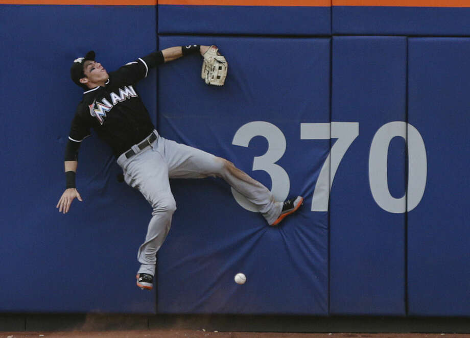 Miami Marlins left fielder Christian Yelich hits the wall while trying to catch a ball hit by New York Mets' Curtis Granderson for an hits an RBI single during the fourth inning of a baseball game Saturday, May 30, 2015, in New York. (AP Photo/Frank Franklin II)
