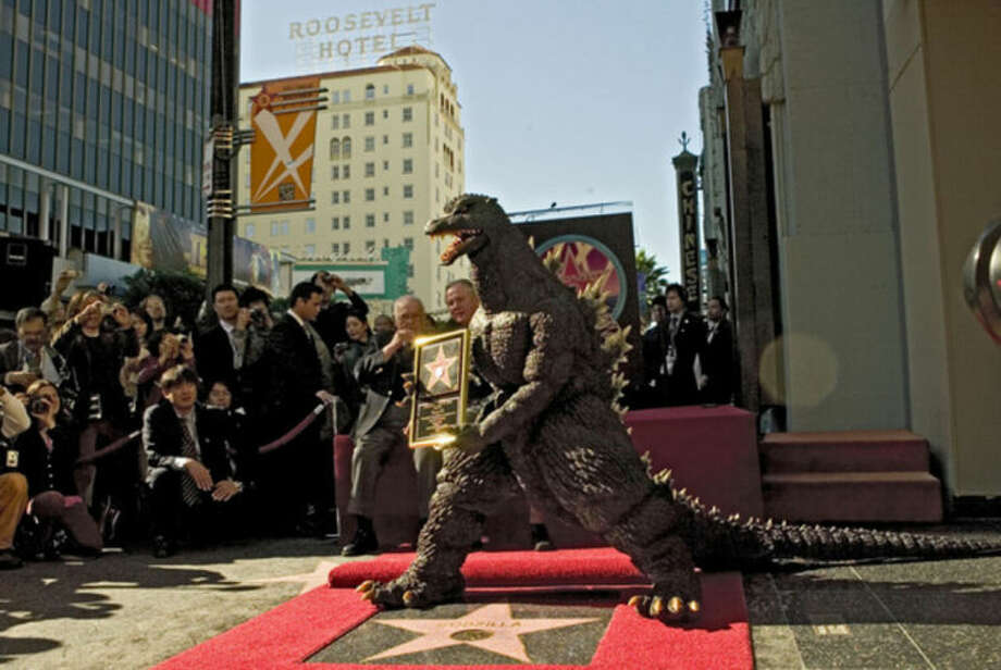 "In this Nov. 29, 2004 file photo, the Godzilla character celebrates its 50th anniversary with a star on the Hollywood Walk of Fame next to the Grauman's Chinese Theatre, now TCL ChineseTheatre, along Hollywood Boulevard, in Los Angeles. Godzilla debuted in Japan in the 1954 film ""Gojira"" but has proven to be just as big of a hitmaker in the United States. (AP Photo/Damian Dovarganes, file)"