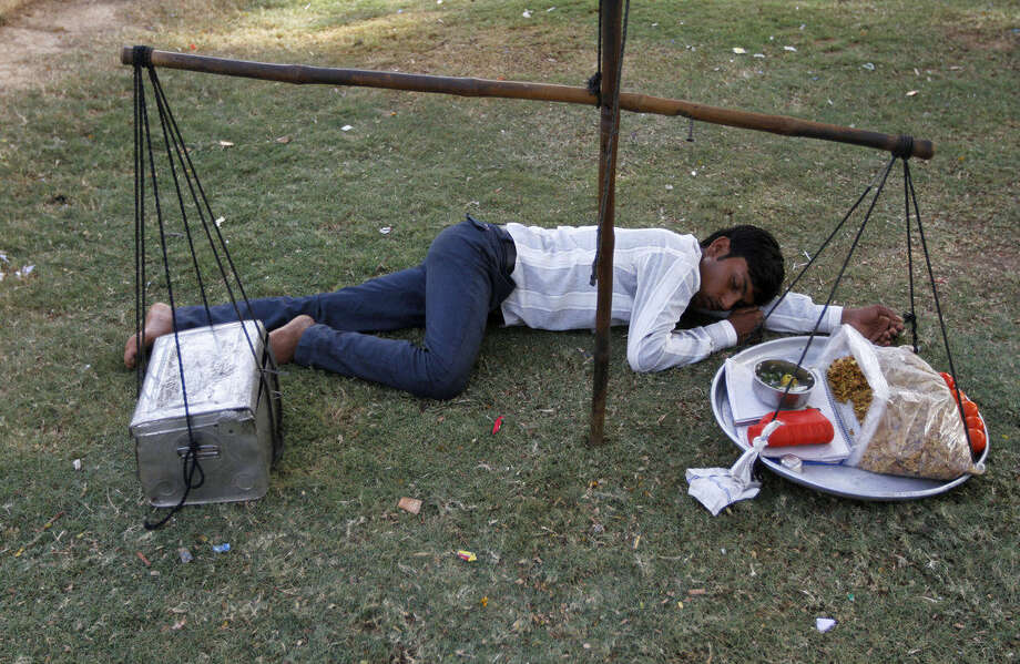 An Indian snacks vendor rests on a lawn on a hot summer day in Ahmadabad, India, Thursday, May 28, 2015. Eating onions, lying in the shade and splashing into rivers, Indians were doing whatever they could Thursday to stay cool during a brutal heat wave that has killed more than 1,000 in the past month. (AP Photo/Ajit Solanki)