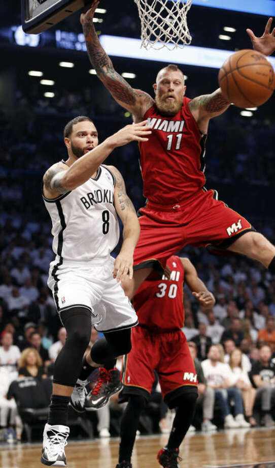 Brooklyn Nets guard Deron Williams (8) passes around Miami Heat forward Chris Andersen (11) in the first half of Game 4 of a second-round NBA playoff basketball game at the Barclays Center, Monday, May 12, 2014, in New York. (AP Photo)