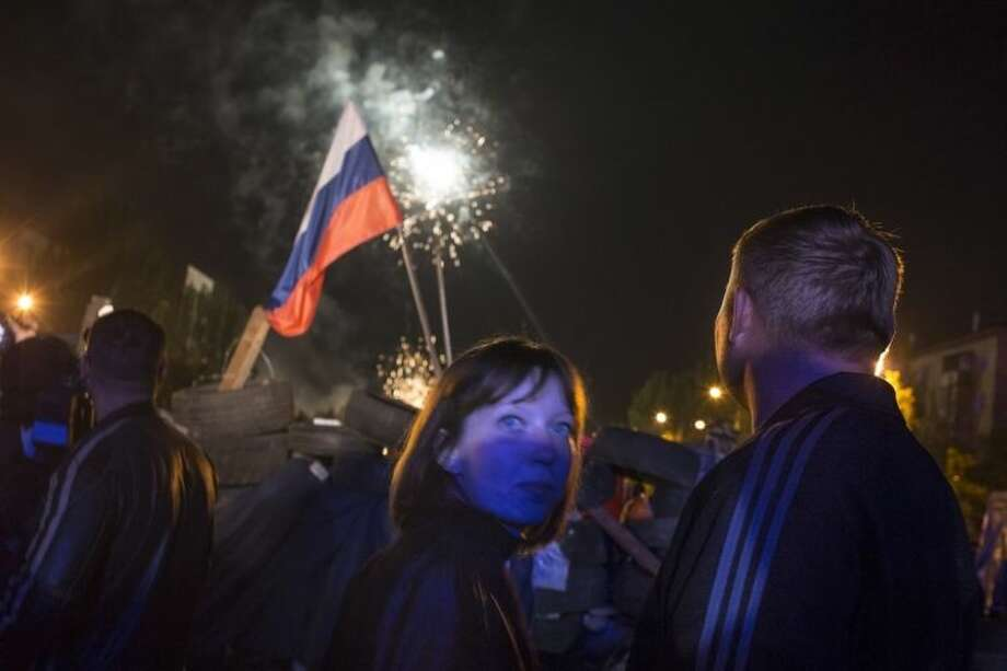 People watch fireworks celebrating the declaration of independence for Donetsk region at barricades in front of a regional administration building that was recently seized by pro-Russian activists in Donetsk, Ukraine, Monday, May 12, 2014, with a Russian national flag in the background. Pro-Moscow insurgents in eastern Ukraine declared independence Monday, putting pressure on Kiev to hold talks with the separatists. (AP Photo/Alexander Zemlianichenko)