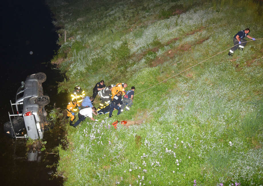 Two men in a pickup truck survived going down a steep embankment and rolling over into the Norwalk River Sunday night at Perry Avenue.