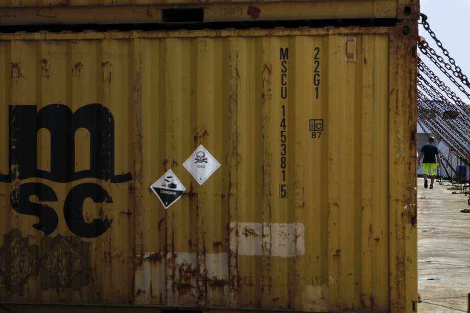 A crew member, right, passes by the containers carrying Syria's dangerous chemical weapons which are being transported out of the strife-torn country, on board the Danish cargo ship Ark Futura in the coastal city of Larnaca, Cyprus, Tuesday, May 13, 2014. Denmark's foreign minister Martin Lidegaard is urging Syria to give up the last of its chemical weapons agents in the next few days in order to meet a June 30 deadline for completely ridding the war-torn country of its lethal stockpile. A Danish-Norwegian flotilla consisting of two warships and two cargo vessels has been moving the chemicals out of Syria for eventual destruction since January. (AP Photo/Petros Karadjias)