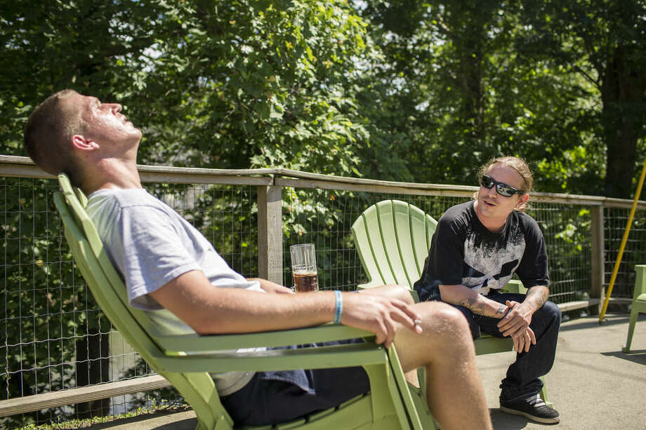 In this May 26, 2015, photo, recovering injection drug users Patton Couch, left, who says he was diagnosed with Hepatitis C, and Justin Kennedy, right, soak up some sun while hanging out at Patton's home where he lives with his parents in Hazard, Ky. Public health officials warn that if the region doesn't get the IV drug abuse problem under control, it's likely to see a Hepatitis C or HIV outbreak. (AP Photo/David Stephenson)