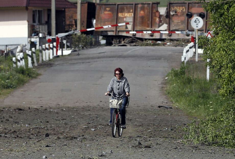 A woman rides a bicycle in front of destroyed barricades on a road leading into Slovyansk, eastern Ukraine, Tuesday, May 13, 2014. Residents of two restive regions in eastern Ukraine engulfed by a pro-Russian insurgency are casting ballots in contentious and hastily organized independence referenda. Sunday's ballots seek approval for declaring so-called sovereign people's republics in the Donetsk and Luhansk regions, where rebels have seized government buildings and clashed with police and Ukrainian troops. (AP Photo/Darko Vojinovic)