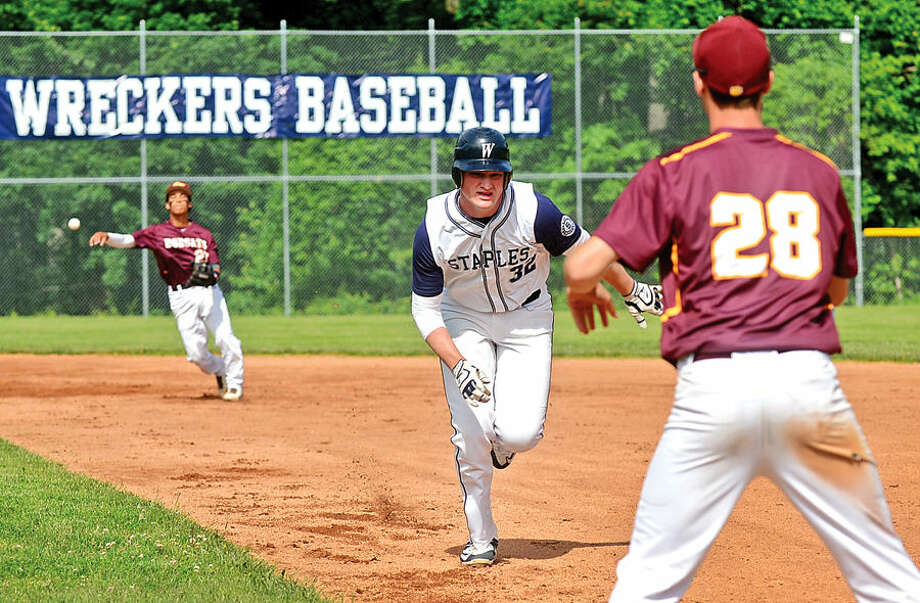Hour photo / Erik Trautmann Staples High School's Ian Burns races back to first to avoid being picked off during their Class LL state tournament game against South Windsor in Westport Thursday.