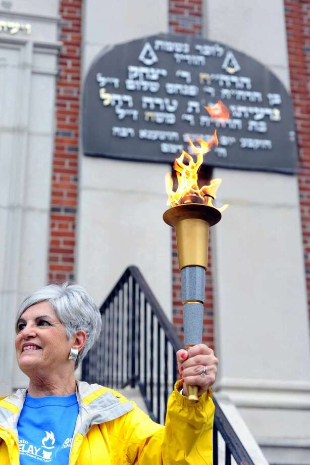 Gail Trell holds the Maccabi Torch while standing in front of Yeshiva Bais Binyomin, on Prospect Street, during the Jewish Community Center of Stamford's Maccabi Torch Relay on Sunday, May 22, 2016.