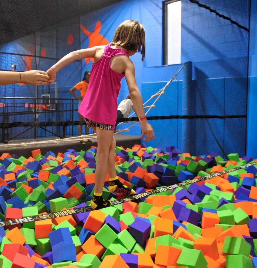 Nina Zaborski, 6, celebrated her birthday at Bounce! Trampoline Sports, in Danbury, on Saturday, the day of their grand opening. She is walking a jib line over a pit of foam blocks. Saturday, May 21, 2016, in Danbury, Conn.