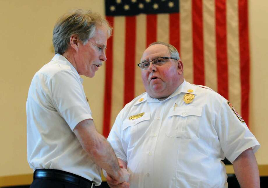 Fire Chief Brian Rooney thanks Deputy Fire Chief Dominick Carfi for his kind words during a gathering to honor Rooney for his 44 years of service to the Bridgeport Fire Department was held at City Hall in Bridgeport, Conn. on Friday, May 20, 2016.