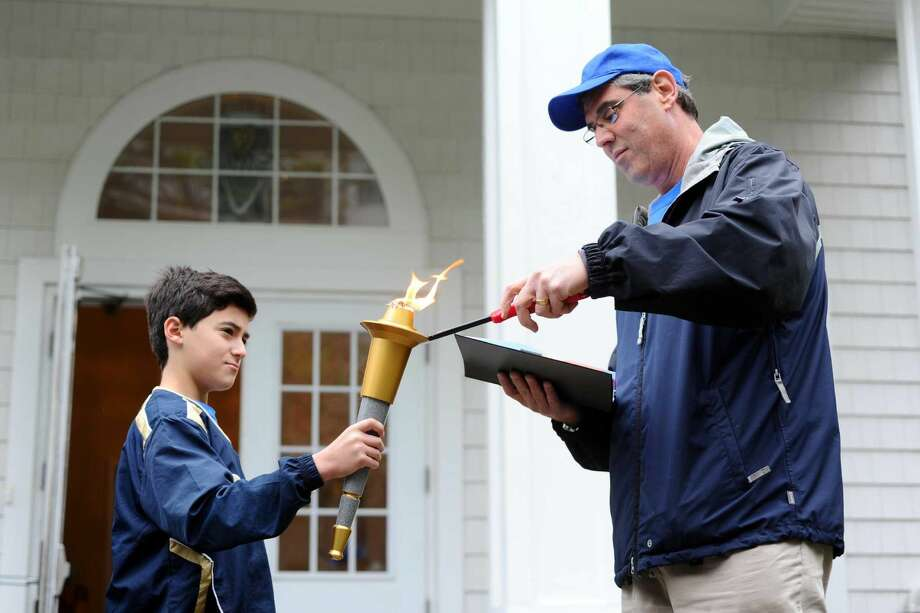 Michael Gold, right, lights the torch in Matthew Vogel's hand to begin the three-hour long relay through Stamford on Sunday, May 22, 2016. The Jewish Community Center of Stamford held the JCC Maccabi Torch Relay, commemorating the JCC's 100th year in Stamford.