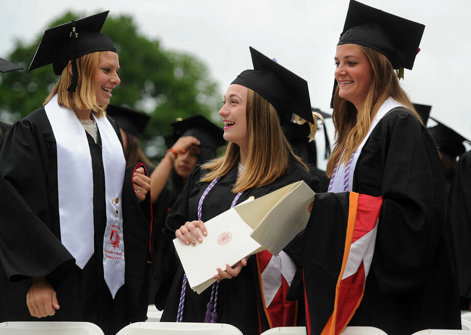 From left; Graduates Elizabeth Ball, of Essex, MA, Emily Baldwin, of Seymour, and Elizabeth Avery, of Hampden, MA, have a laugh as they take their seats for the Fairfield University graduation in Fairfield, Conn. on Sunday, May 22, 2016.