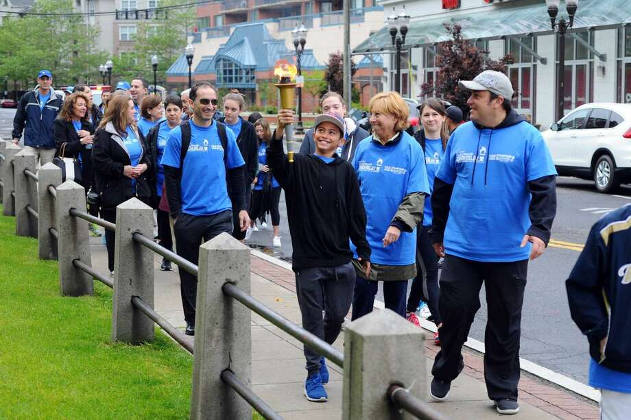 Benji Fuchs smiles as he walks the Maccabi Torch down Forest Street on Sunday, May 22, 2016 as part of the Jewish Community Center of Stamford's JCC Maccabi Torch Relay, which commemorates the JCC's 100th year in the city.