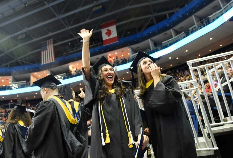 Karla Sansone, left, of Stratford, and Carinne Cort-Real, of Danbury, look to the audience during the Western Connecticut State University commencement ceremony at Webster Bank Arena in Bridgeport, Conn. Sunday, May 22, 2016. More than 800 of the university's 1,235 eligible undergraduate candidates participated in the ceremony, along with more than 60 graduate candidates.