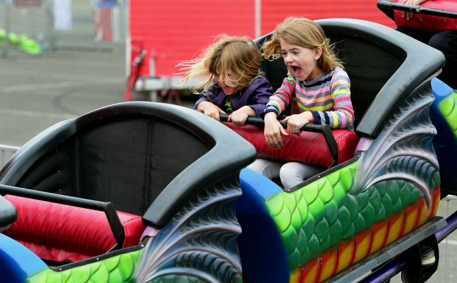 Lydia Dillon, 4, and her big sister Cece, 6, enjoy a ride on the Dragon Wagon during the Holy Family Carnival at the Jennings Beach parking lot in Fairfield, Conn., on Saturday May 21, 2016. The carnival continues Sunday from 1 p.m. to 5 p.m.
