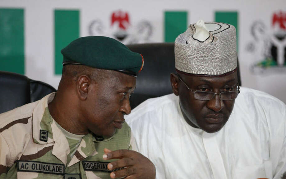 Brig. Gen. Chris Olukolade, Nigeria's top military spokesman, left, talks with Director General, National Orientation Agency, Mike Omeri, during a press conference on the abducted school girls in Abuja, Nigeria, Monday, May 12, 2014. A Nigerian Islamic extremist leader says nearly 300 abducted schoolgirls will not be seen again until the government frees his detained fighters. A new video from Nigeria's homegrown Boko Haram terrorist network received Monday purports to show some of the girls and young women chanting Quranic verses in Arabic. The barefoot girls look frightened and sad and sit huddled together wearing gray Muslim veils. Some Christians among them say they have converted to Islam. (AP Photo/Sunday Alamba)