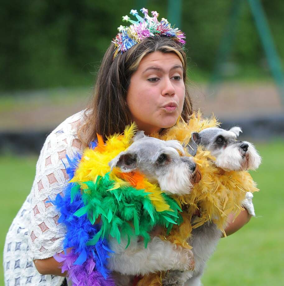 Mariana Lopez, of Stamford, makes a funny face while having a photo taken with her terriers Archie and Shakira Mafalda during the third annual Doggy Day Palooza at the Stamford Dog Park on Saturday.