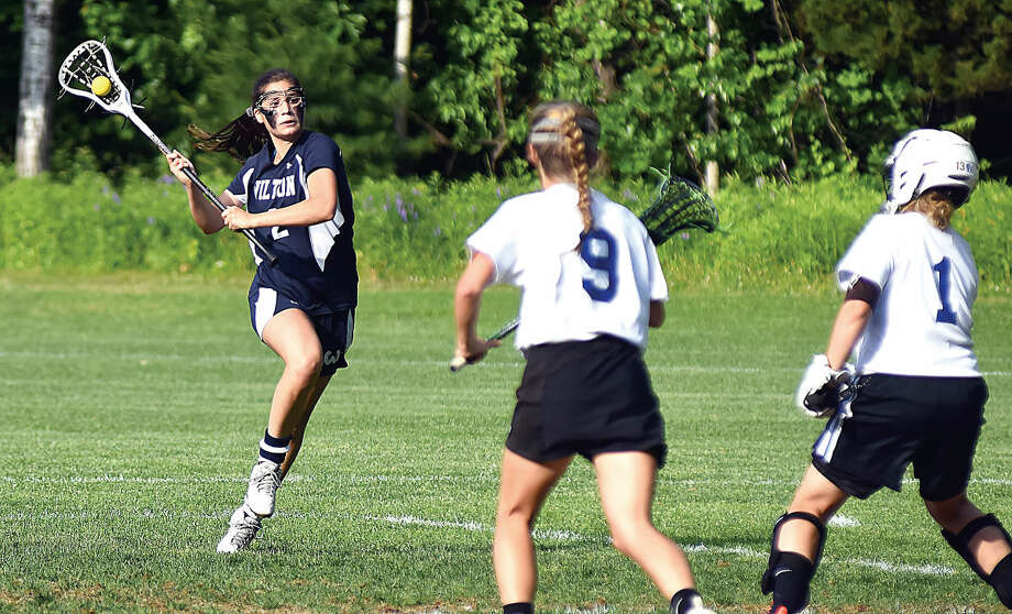 Hour photo/John Nash - Rebecca Wistreich, left, of Wilton rears back to take a shot on Glastonbury goalie Audrey Apanovitch as the Tomahawks' Bryn Murray (9) looks on during Thursday's CIAC Class L quarterfinal.