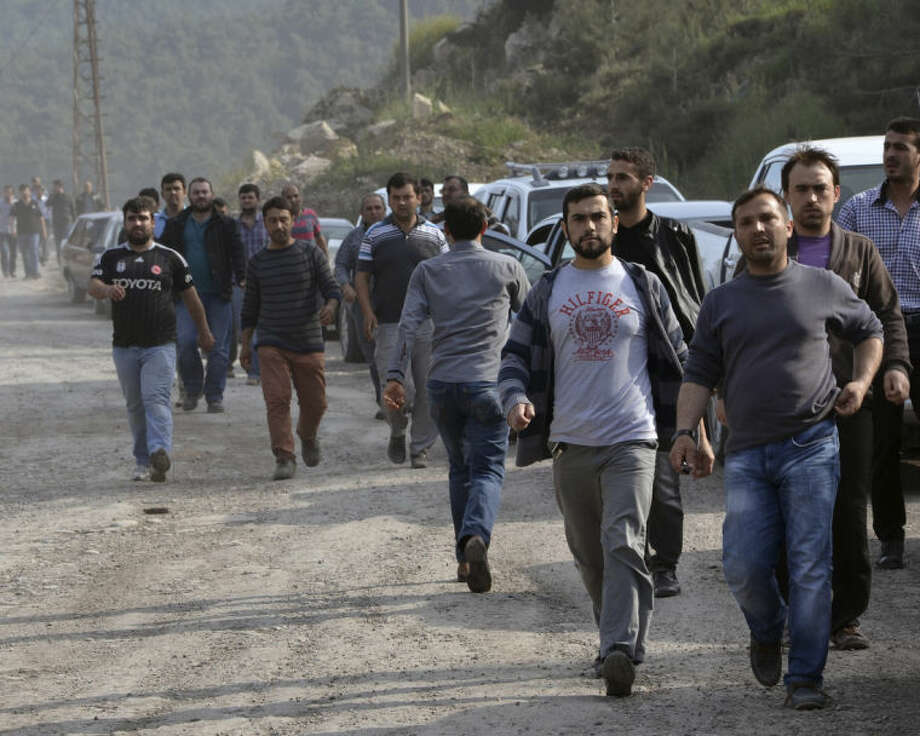 Workers and relatives arrive after an explosion and fire at a coal mine in Soma, in western Turkey, Tuesday, May 13, 2014. An explosion and fire at a coal mine in western Turkey killed at least one miner Tuesday and left up to 300 workers trapped underground, a Turkish official said. Twenty people were rescued from the mine in the town of Soma in Manisa province but one later died in the hospital, Soma administrator Mehmet Bahattin Atci told reporters. The town is 250 kilometers (155 miles) south of Istanbul. (AP Photo/IHA) TURKEY OUT