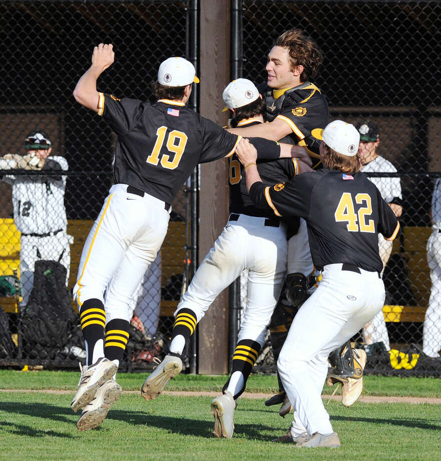 Brunswick relief pitcher Trevor Johnson, center is mobbed by teammates, from left, Mike Beninati (19), Nick Mosher (42) and catcher Wilson Salomon after the Bruins beat Hamden Hall for their second straight FAA championship.