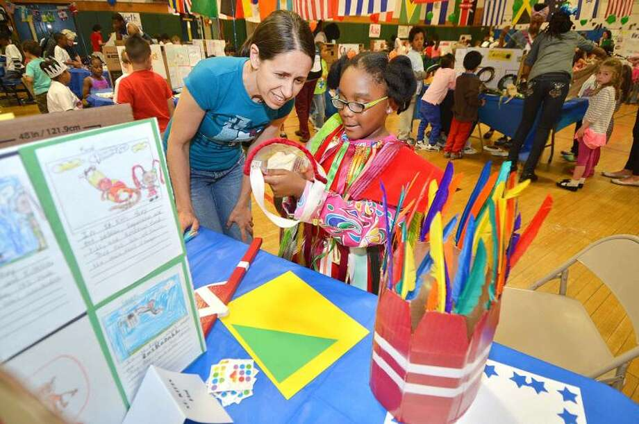 Hour Photo/Alex von Kleydorff Teacher Sue Zanonne admires the traditional St. Kitts clothing worn by 2nd grader Naiya Phipps during Columbus Magnet School's Culture Connection