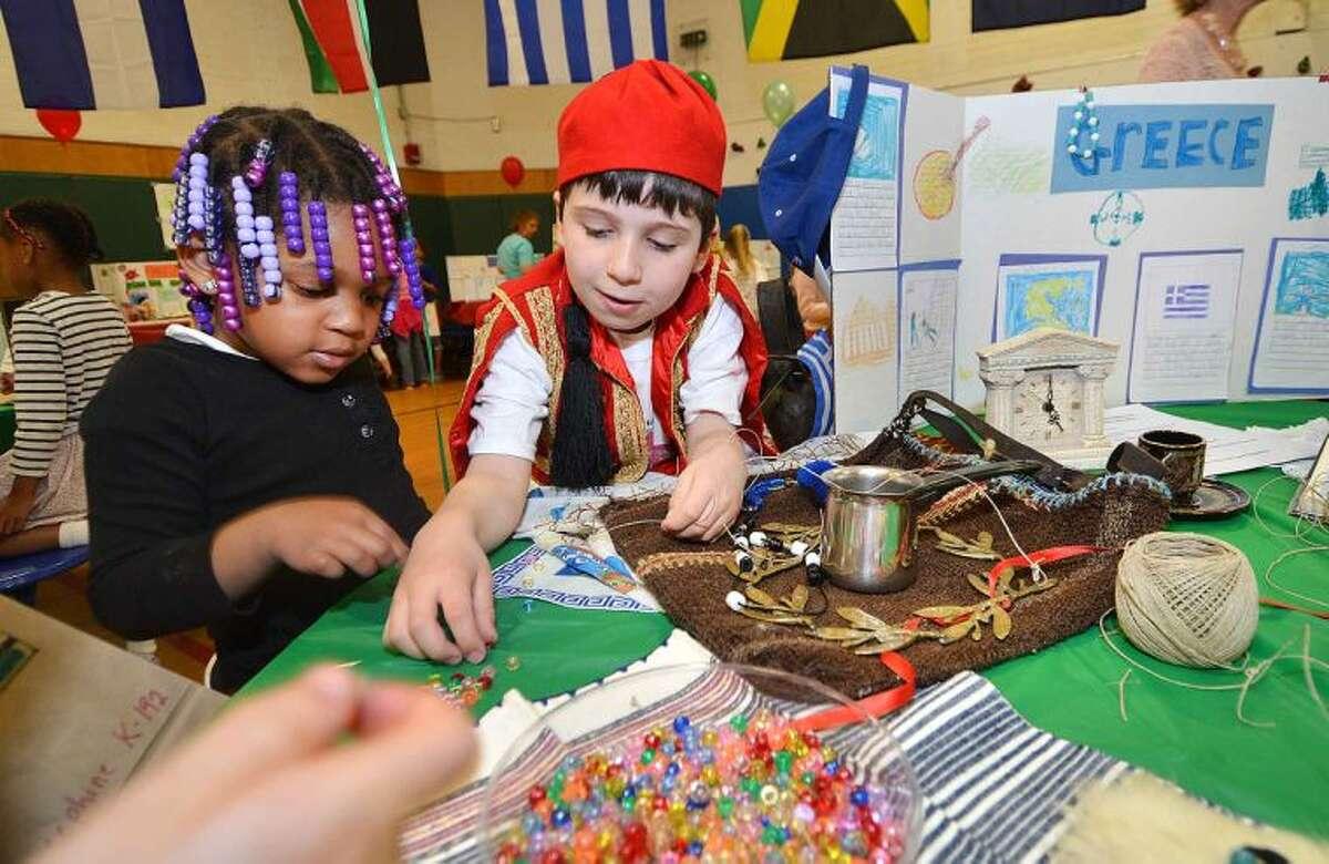 Hour Photo/Alex von Kleydorff Niarra Hall helps William Traub make sets of Greek Worry Beads during Columbus Magnet Schools Culture Connection