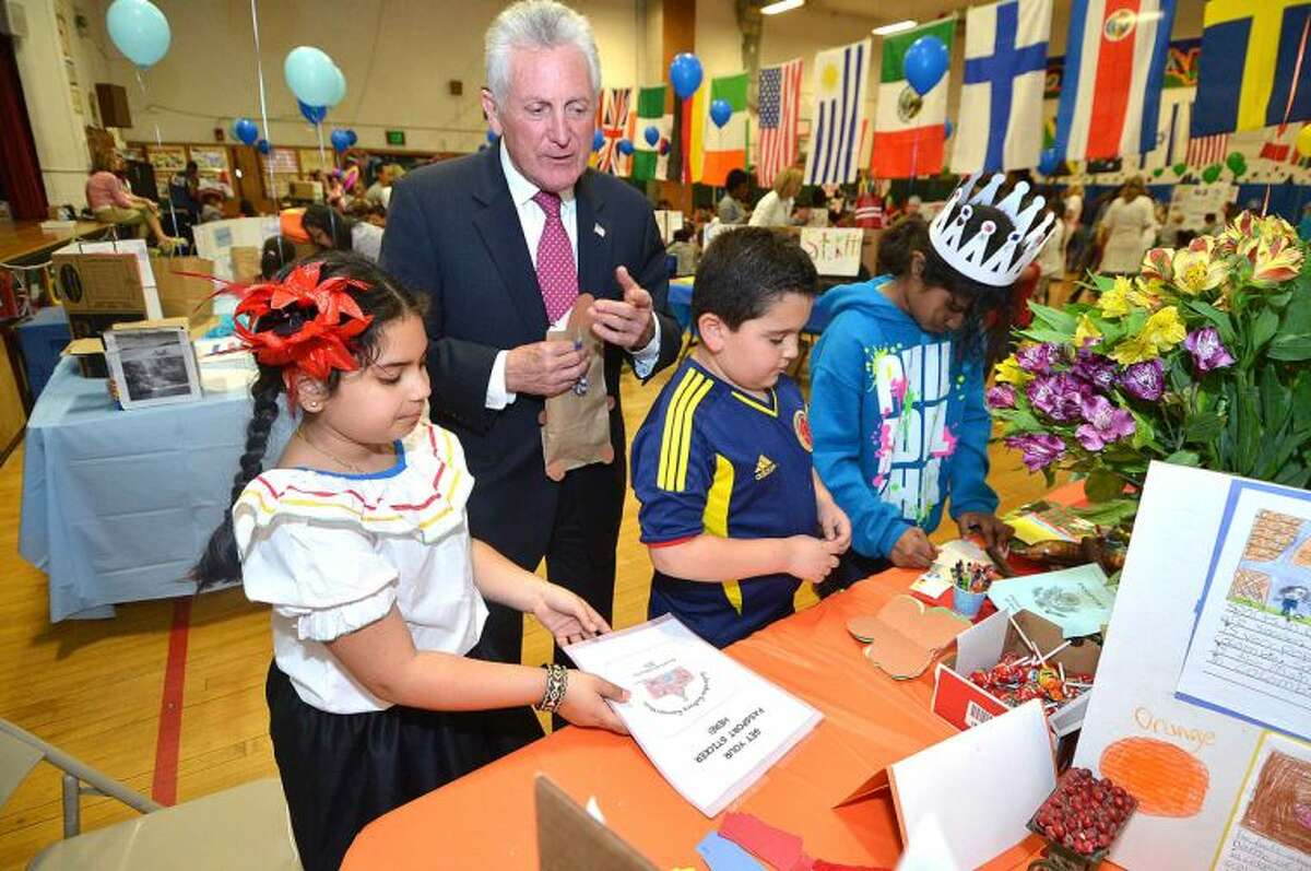 Hour Photo/Alex von Kleydorff . Mayor Harry Rilling gets his passport stamped and learns about Columbia from 2nd graders Julissa Acosta and David Mandujano during Columbus Magnet School's Culture Connection on Tuesday