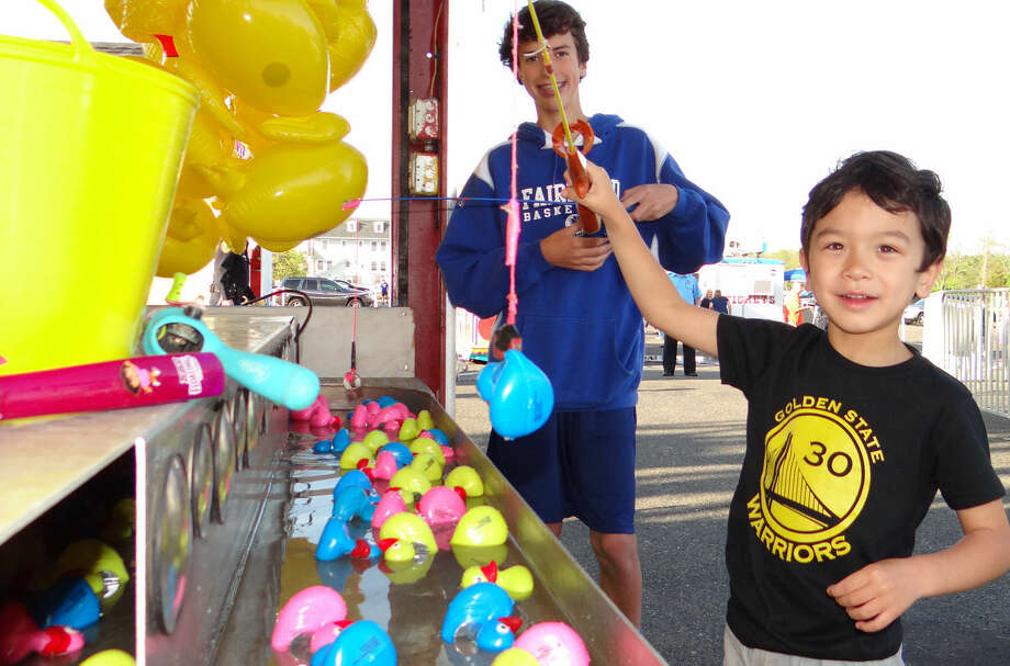Jake and Sam Sweeney, ages 4 and 14, of Fairfield, try their luck at the Lucky Duck challenge at the Holy Family Church carnival.