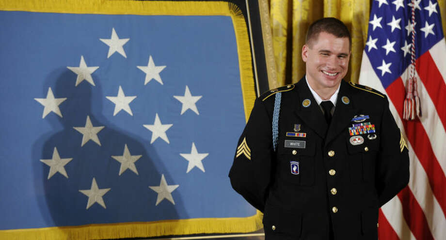 Former Army Sgt. Kyle J. White smiles as President Barack Obama talks about him before he was awarded the Medal of Honor during a ceremony in the East Room of the White House in Washington, Tuesday, May 13, 2014. White is a former Army sergeant who saved a fellow soldier's life and helped secure the evacuation of other wounded Americans while under persistent fire during a 2007 ambush in Afghanistan. White is the seventh living recipient to be awarded the Medal of Honor for actions in Iraq or Afghanistan. (AP Photo)