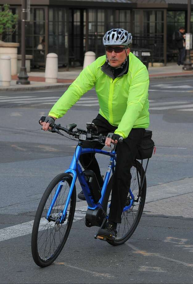 """Jack Chnowski, an employee with the City of Stamford, rides over on an e-bike to a """"Bike to Work Day"""" event at Veteran's Park in Stamford on Friday. Chnowski, who is in his his early 60s, uses the electric-powered bike to commute around downtown Stamford."""