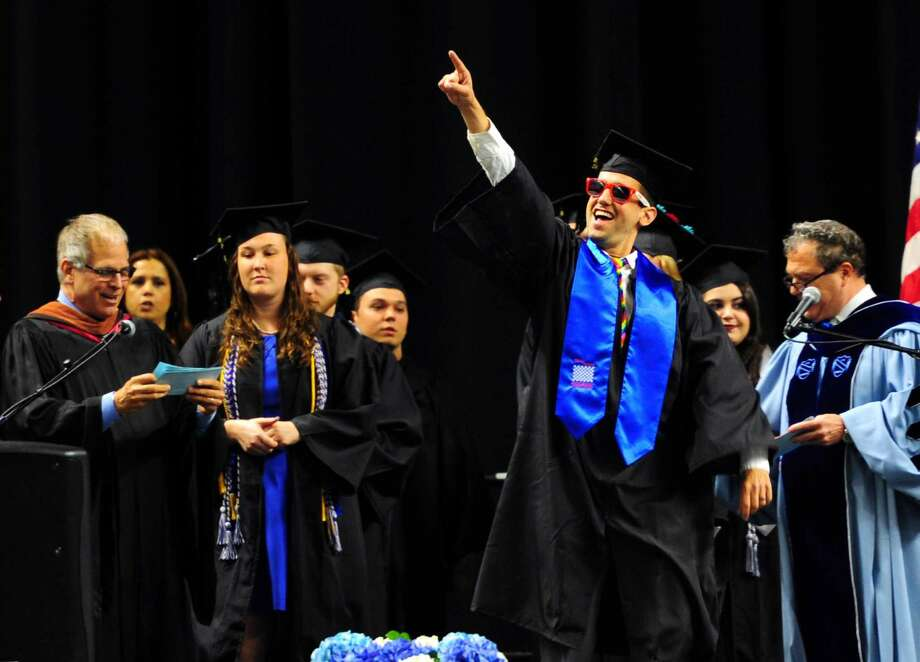 Jason Riddle, of Shelton, points to his family as he walks onstage to get his diploma during Southern Connecticut State University's Commencement 2016 Undergraduate Ceremony at the Arena at Harbor Yard in Bridgeport on Friday.