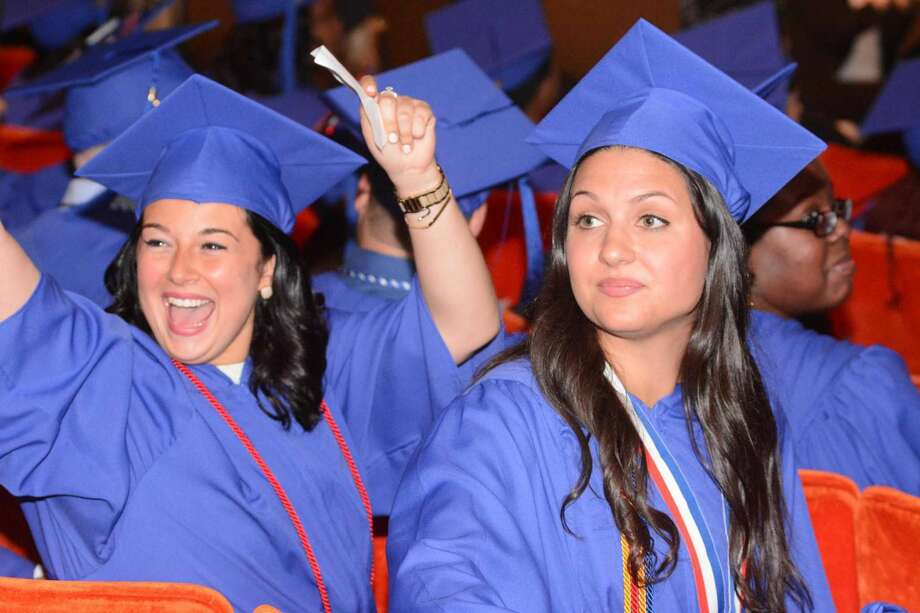 Jessica Guidone from Branford, left, and Brigida LoMonaco from Madison watch as their fellow graduates enter the hall during St. Vincent College Commencement ceremony that took place at University of Bridgeport on Friday May 20, 2016.