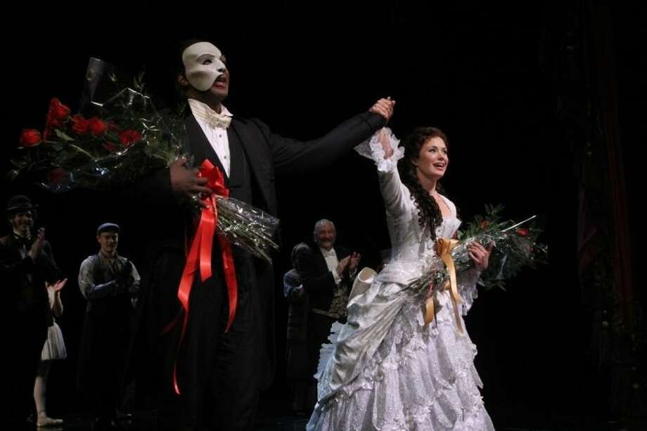 """This May 12, 2014 photo released by The Publicity Office shows Norm Lewis, left, and Sierra Boggess acknowledging applause on the pair's opening night with the Broadway production of The Phantom of the Opera at The Majestic Theatre, in New York. Lewis is the first African-American actor to take on the title role in Broadway's """"The Phantom of the Opera."""" (AP Photo/The Publicity Office, Bruce Glikas)"""
