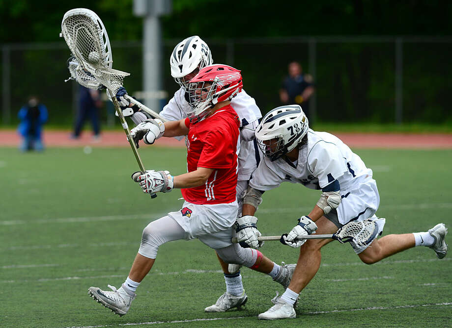 Cardinal Goalie Bennett Cooper is swarmed by Wreckers Michael Reale and Ross Goldberg as the Greenwich High School Boys Lacrosse team takes on Staples in their FCIAC boys lacrosse playoff game in Westport, Conn. Saturday, May 21, 2016.