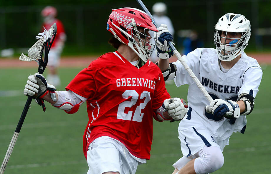 #22 William Baugher of the Greenwich High School Boys Lacrosse team moves the ball up field past Bill Hutchinson in their FCIAC boys lacrosse playoff game against Staples High School in Westport, Conn. Saturday, May 21, 2016.
