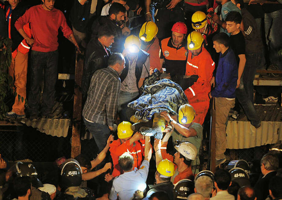 Miners carry a rescued friend hours after an explosion and fire at a coal mine killed at least 17 miners and left up to 300 workers trapped underground, in Soma, in western Turkey, late Tuesday, May 13, 2014, a Turkish official said. Twenty people were rescued from the mine but one later died in the hospital, Soma administrator Mehmet Bahattin Atci told reporters. The town is 250 kilometers (155 miles) south of Istanbul. The death toll was expected to rise.(AP Photo)