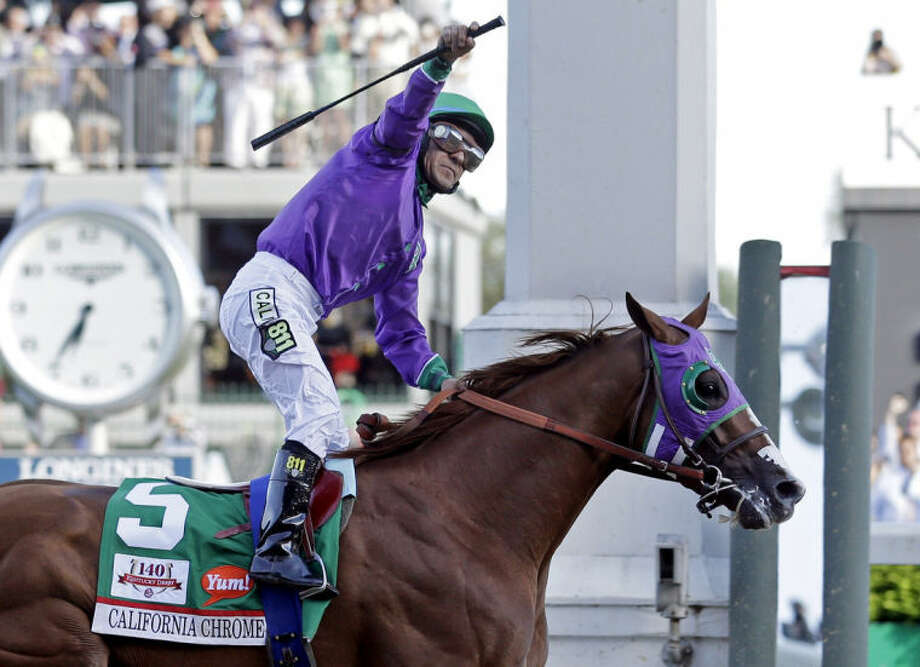 FILE - In this May 3, 2014, file photo, jockey Victor Espinoza celebrates aboard California Chrome after winning the 140th running of the Kentucky Derby horse race at Churchill Downs in Louisville, Ky. The California colt will be running in the Preakness with a bulls-eye on his back as perhaps racing's next superstar. He figures to face eight or nine rivals in the middle leg of the Triple Crown series, and one of them might be a filly. (AP Photo/Morry Gash, File)