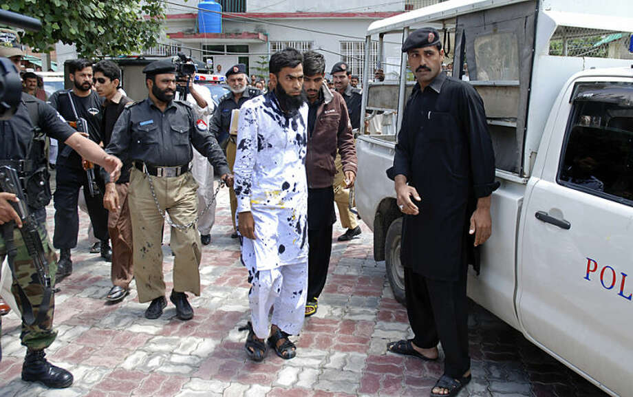 Pakistani suspects of a gang rape, center, leave a court after outraged citizens pelted the suspects with ink and tomatoes, in Mansehra, Pakistan, Wednesday, May 14, 2014. Pakistani police have arrested a seminary teacher and two of his friends on charges of gang raping a college girl in a city in the northwest, a police official said Wednesday. The case is unusual since rape cases are rarely prosecuted in Pakistan and women who complain are often stigmatized. (AP Photo/Aqeel Ahmad)