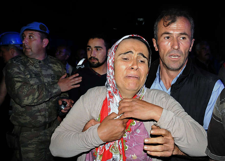 Family members gather near the mine after an explosion and fire at a coal mine killed at least 17 miners and left up to 300 workers trapped underground, in Soma, in western Turkey, Tuesday, May 13, 2014, a Turkish official said. Twenty people were rescued from the mine but one later died in the hospital, Soma administrator Mehmet Bahattin Atci told reporters. The town is 250 kilometers (155 miles) south of Istanbul. The death toll was expected to rise.(AP Photo/Depo Photos)