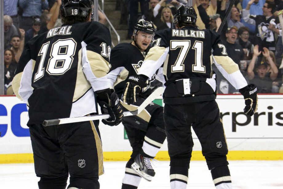 Pittsburgh Penguins' Jussi Jokinen (36) celebrates his goal with teammates Evgeni Malkin (71) and James Neal (18) in the second period of Game 7 of a second-round NHL playoff hockey series against the New York Rangers, in Pittsburgh on Tuesday, May 13, 2014. (AP Photo)