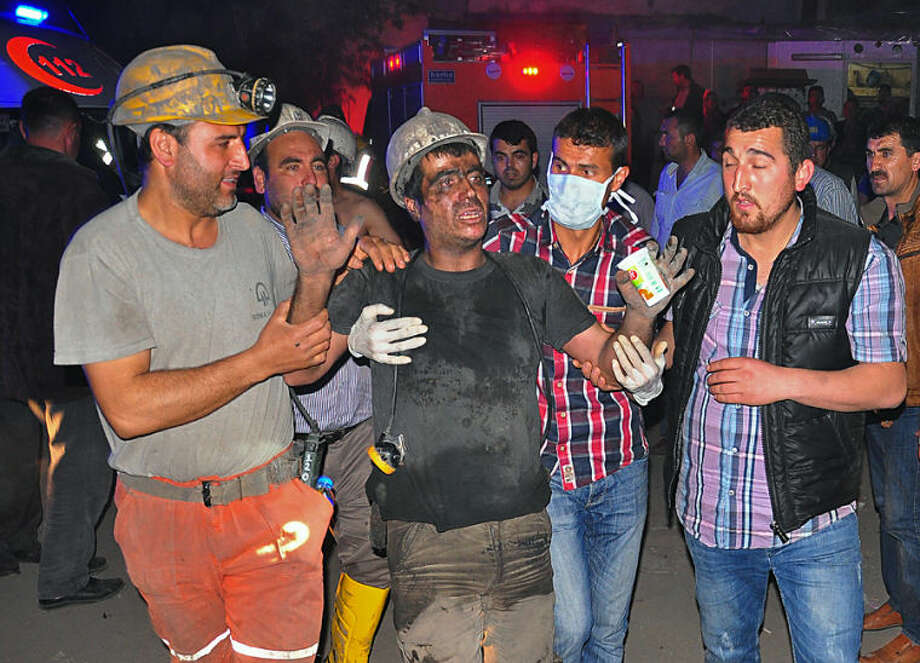Miners escort a rescued friend after an explosion and fire at a coal mine in Soma, in western Turkey, Tuesday, May 13, 2014. An explosion and fire at a coal mine in western Turkey killed at least one miner Tuesday and left up to 300 workers trapped underground, a Turkish official said. Twenty people were rescued from the mine in the town of Soma in Manisa province but one later died in the hospital, Soma administrator Mehmet Bahattin Atci told reporters. The town is 250 kilometers (155 miles) south of Istanbul. (AP Photo/IHA)