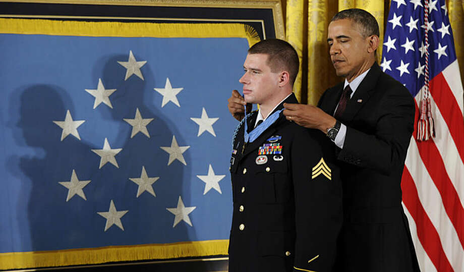 President Barack Obama awards the Medal of Honor to former Army Sgt. Kyle J. White during a ceremony in the East Room of the White House in Washington, Tuesday, May 13, 2014. White is a former Army sergeant who saved a fellow soldier's life and helped secure the evacuation of other wounded Americans while under persistent fire during a 2007 ambush in Afghanistan. White is the seventh living recipient to be awarded the Medal of Honor for actions in Iraq or Afghanistan. (AP Photo)