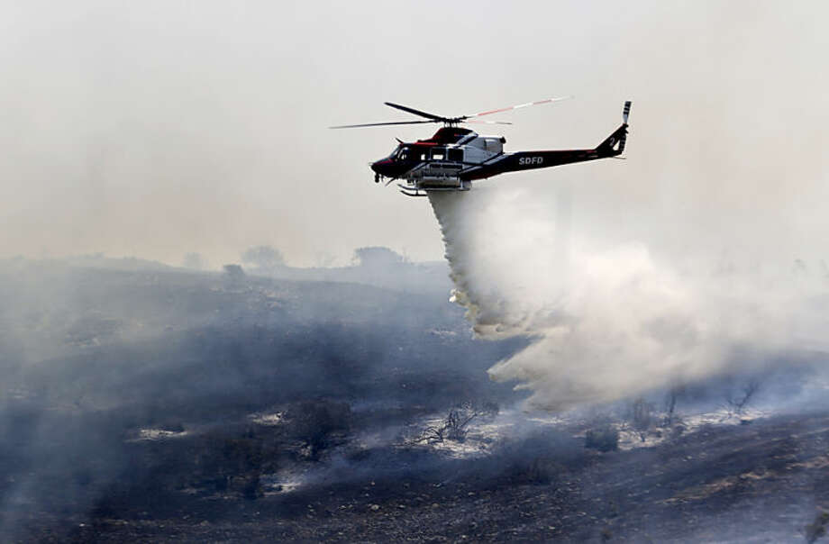 A helicopter attacks a wildfire burning in the north county of San Diego Tuesday, May 13, 2014, in San Diego. Wildfires pushed by gusty winds chewed through canyons parched by California's drought, prompting evacuation orders for more than 20,000 homes on the outskirts of San Diego and another 1,200 homes and businesses in Santa Barbara County 250 miles to the north. (AP Photo)