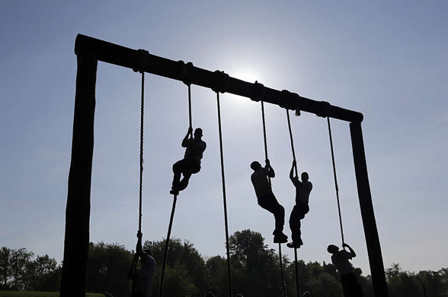 Freshman midshipmen, known as plebes, climb ropes on an obstacle course during Sea Trials, a day of physical and mental challenges that caps off the freshman year at the U.S. Naval Academy in Annapolis, Md., Tuesday, May 13, 2014. (AP Photo/Patrick Semansky)