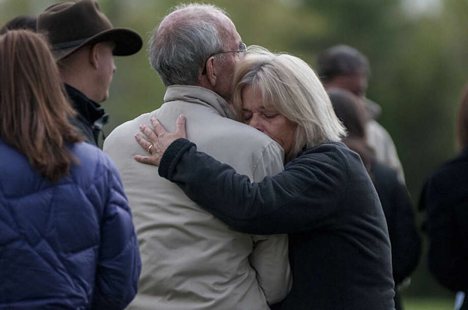 Family members and friends embrace during a candlelight vigil for slain Brentwood, N.H. police officer Stephen Arkell in Brentwood, Tuesday, May 13, 2014. According to authorities, Arkell was fatally shot by suspected gunman, Michael Nolan, 47, who later died in a roaring house fire. Authorities said Arkell had been invited into the home by the gunman's father during an argument and was immediately cut down without a chance to draw his weapon. (AP Photo/Foster's Daily Democrat, Ryan McBride)