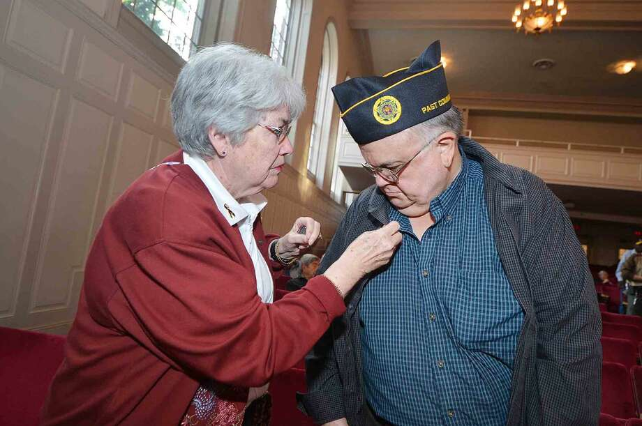 Vietnam era veteran Ron Aarons gets his commemorative pin placed on his lapel by Mary Keegans during the Veterans Hall of Honor Dedication Ceremony at Norwalk City Hall in Norwalk Conn. May 22 2016
