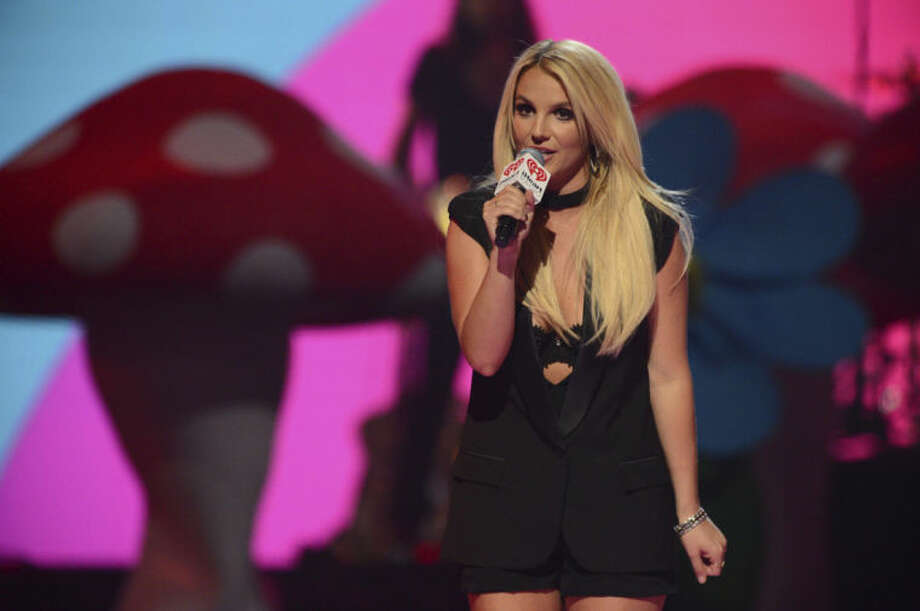 "FILE - In this Sept. 21, 2013 file photo, Britney Spears introduces Miley Cyrus at IHeartRadio Music Festival, day 2, in Las Vegas. The ""Now That's What I Call Music"" series reached No. 50 in early May 2014, and also will include a bonus disc of fan-voted hits that include top ""Now"" stars like Spears, Katy Perry, Rihanna and Swift. (Photo by Al Powers/Powers Imagery/Invision/AP, file)"